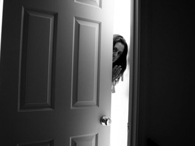 woman slowly opening door