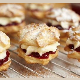 A sandwich of buttercream and jam between two cookies