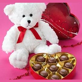 A teddy bear holding a box of chocolates