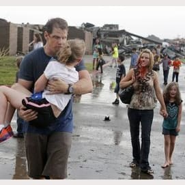 An injured family walks away from their destroyed neighborhood in Moore, Oklahoma