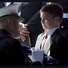 A little boy is given the U.S. flag at his soldier father's funeral