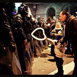 A Romanian child hands a heart-shaped balloon to riot police during protests against austerity measures in Bucharest