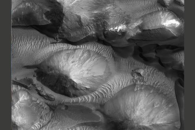 Este enorme cañón de aproximadamente 250 kilómetros de largo y 100 kilómetros de ancho, al norte de Valles Marineris, está parcialmente cubierto de dunas.