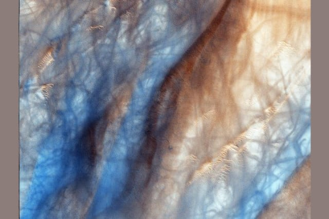 Estos torbellinos de arena desplazan la fina capa de polvo de la superficie marciana dejando expuesta una región oscura. Las huellas azules corresponden a las marcas que deja a su paso este fenómeno.