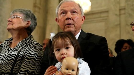 Sessions brought his young grandchildren to the hearing, as protesters dressed as KKK members gathered outside. Sen Cory Booker