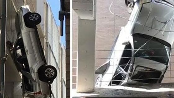 A driver escaped unharmed after he lost control of his car and ended up dangling mid-air from a multi-storey car park in Austin, Texas on Friday, September 9. Incredibly, a high-tension wire became caught in one of the wheels and prevented the car from plummeting to the ground. The 24-year-old driver was then able to climb back into the building with the help of a bystander. http://www.iplaybuzz.com