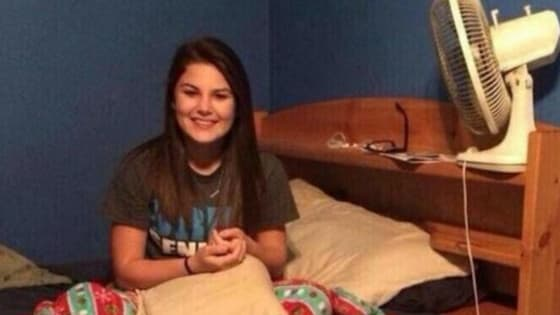 A man came home early from a business trip to find his wife sitting politely in bed. He took a photo of her to capture her surprise about his early return.