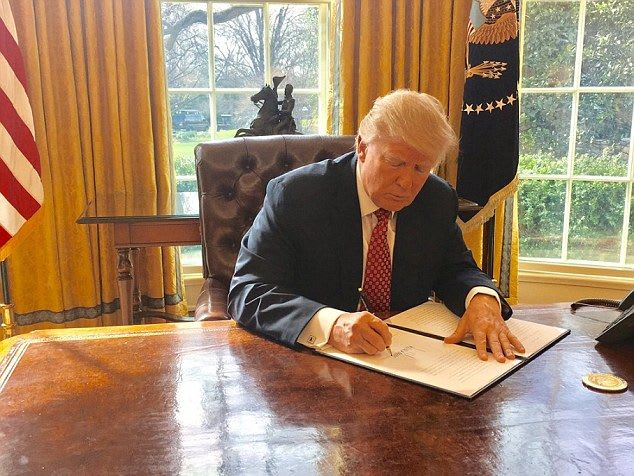 Trump signs the order in the Oval Office