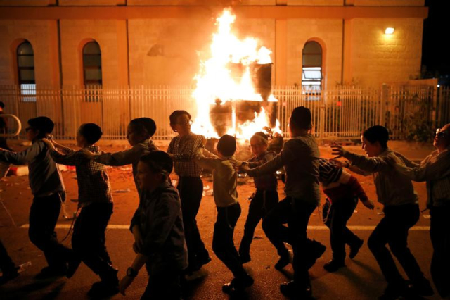 Children dance around a bonfire as they celebrate the Jewish holiday of Lag Ba'omer in the city of Ashdod, May 22, 2019. (Credit: Amir Cohen / Reuters)