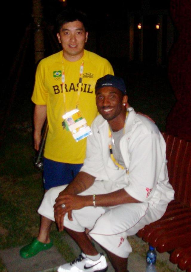 """""""Eu também adorava acompanhar os jogos dos Los Angeles Lakers, da NBA, desde a época do Magic Johnson. E sabia que o Kobe Bryant estava lá, com o Dream Team. Estava eu voltando do jantar, chegando perto do nosso prédio, vi uma pequena muvuca. Quando pude ver o que estava acontecendo, simplesmente era o Kobe, tirando fotos com a galera! Não sei o que ele estava fazendo lá, nem quis saber, só queria tirar uma foto com ele. Fiquei na fila, e quando chegou a minha vez, ele sentou no banco. Fiquei ao lado dele e tirei a foto. Logo depois da minha foto, seu segurança falou para a galera que ele queria descansar. Fui o último a tirar a foto! Infelizmente, em 2020, ele se foi naquele acidente de helicóptero! Fiquei em choque quando apareceu no meu celular a manchete do acidente, e que ele havia falecido""""."""