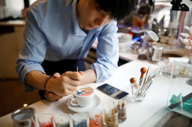 El artista busca la imagen deseada en internet y la copia directamente sobre la taza de café.