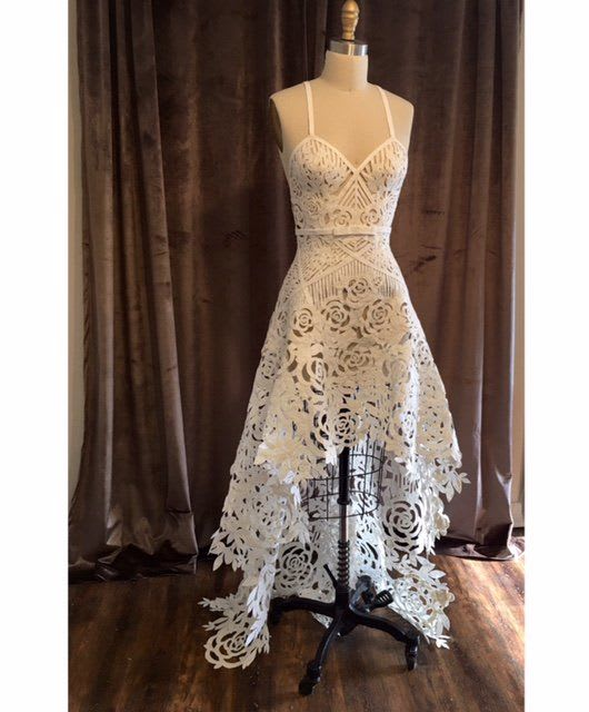 This unbelievable sheer gown submitted by Ashley Ulcini Cobb features geometric and rose cutouts throughout and rides the trend of high-low skirts flawlessly. The sharp bow belt detail at the front of the dress only adds to its uber-detailed perfection.