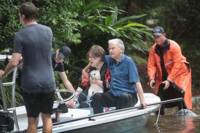 Here, an elderly woman clings to her poodle as the whole family is rescued by an emergency crew.
