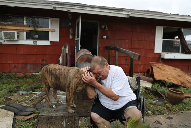 A man holds his dog and weeps outside the wreckage of their home.