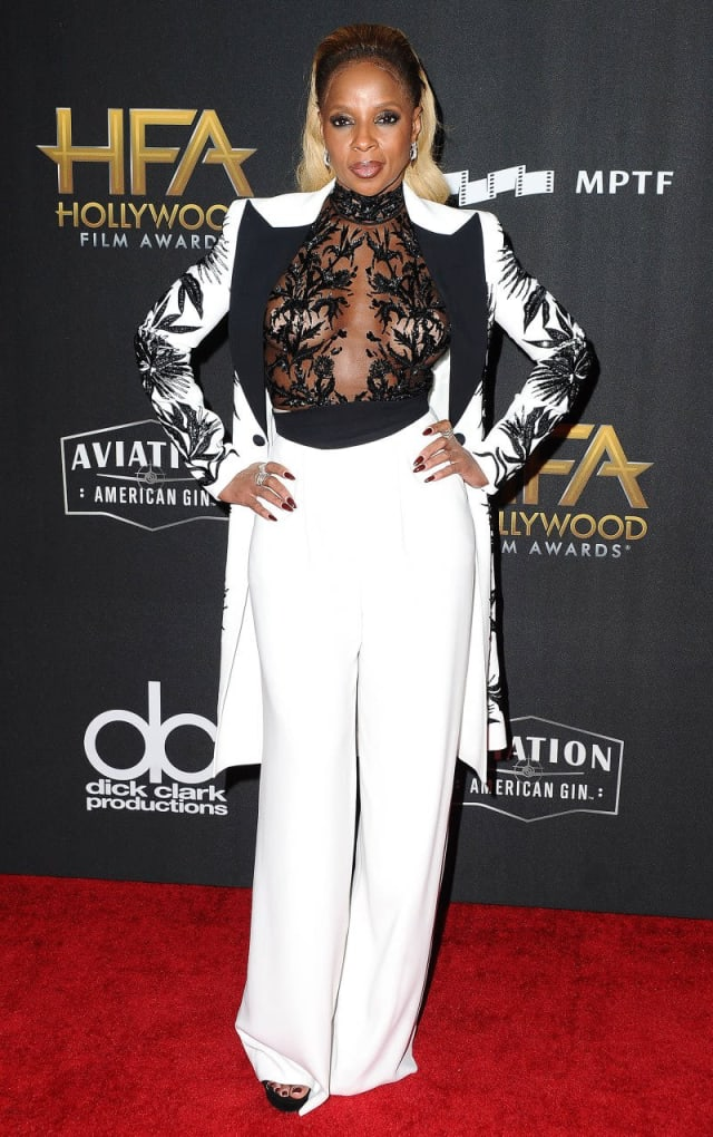 Mary J. Blige looking fierce as can be In a mesh top with beaded embellishments, white high-waist pants and a white and black matching jacket.