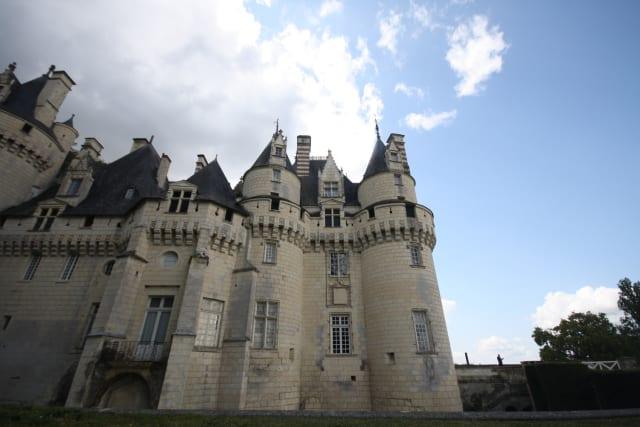 De AzayLe Rideau a Chinon Se Tours é movimentada e relativamente grande, Azay Le Rideau, onde passamos a segunda noite, é um charmoso povoado de interior. Com 3.500 habitantes e ruas tranquilas, pode ser explorada em uma pequena caminhada – vai ser bom para descansar dos pedais e esticar as pernas.O Château d'Azay-le-Rideau , erguido no século 16, não está entre os mais famosos do Vale do Loire . Mas fica dentro da cidade, em uma ilha do Rio Indre. Assim, se você for daqueles obcecados por castelos, não perca a chance e o visite também. Se não for seu caso, faça como a gente: pelo menos dê uma espiada pelo lado de fora.Os 34 quilômetros entre Azay Le Rideau a Chinon foram um passeio pela França rural, que muitas vezes parecia congelada no tempo, um retrato daqueles filmes europeus de época. O trecho é cheio de plantações, sobretudo de uva e maçã, e pequenas propriedades com cavalos, bois, carneiros.No percurso praticamente não havia ciclovias. Mas nos sentimos muito seguros pedalando pelas estradinhas – sempre havia outros ciclistas pelo caminho e os carros costumavam ser respeitosos.Cerca de 12 quilômetros depois do início do trajeto, à esquerda da estrada já podíamos avistar o castelo – dentre os da região, o mais interessante para crianças. Trata-se do Château d'Ussé , o mesmo que inspirou Charles Perrault a, no século 17, escrever a história da Bela Adormecida . Ingresso a 14 euros (R$ 60).A primeira construção no local, às margens do Rio Indre, data do século 11. Várias ampliações, reformas e complementos foram dando ao castelo a forma atual, ao gosto de cada novo proprietário da mansão. A consolidação de seu desenho, tal e qual hoje em dia, é resultado de obras realizadas ao longo do século 19.Em um percurso pelos andares que dão acesso à torre principal, a história da Princesa Aurora é contada, cena a cena, com recriações de ambientes e personagens, estáticos, do famoso conto de fadas. Em cada sala, uma página de livro exibe o trecho – em francês e inglês – r