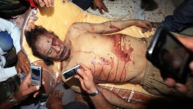 Fotografías tomadas por rebeldes libios con sus teléfonos móviles del cadáver de Gadafi; La Vanguardia .-
