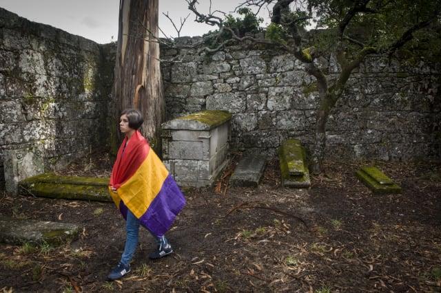 Una mujer envuelta en la bandera de la Segunda República española, en un cementario de la isla San Simón