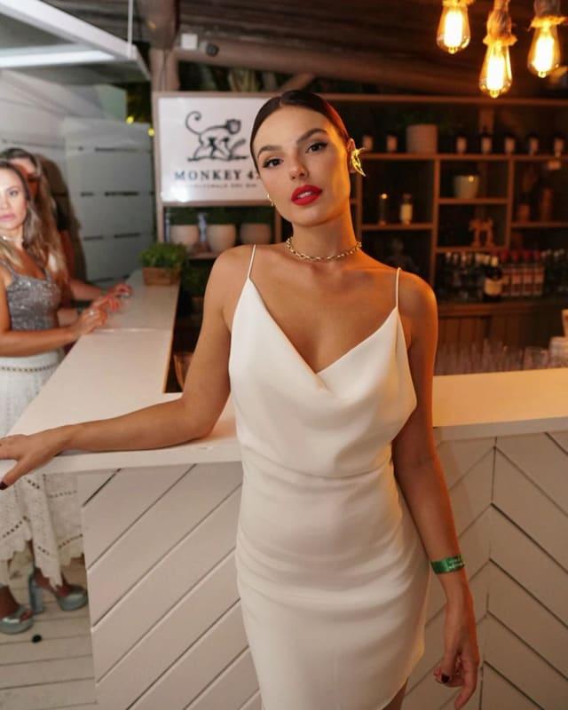 O minimalismo foi a escolha de Isis Valverde, que escolheu vestido branco sem frescuras e com elegância de sobra. Caprichou nos acessórios, como a gargantilha delicada e o ear cuff. O batom vermelho levou um ponto de cor ao look.