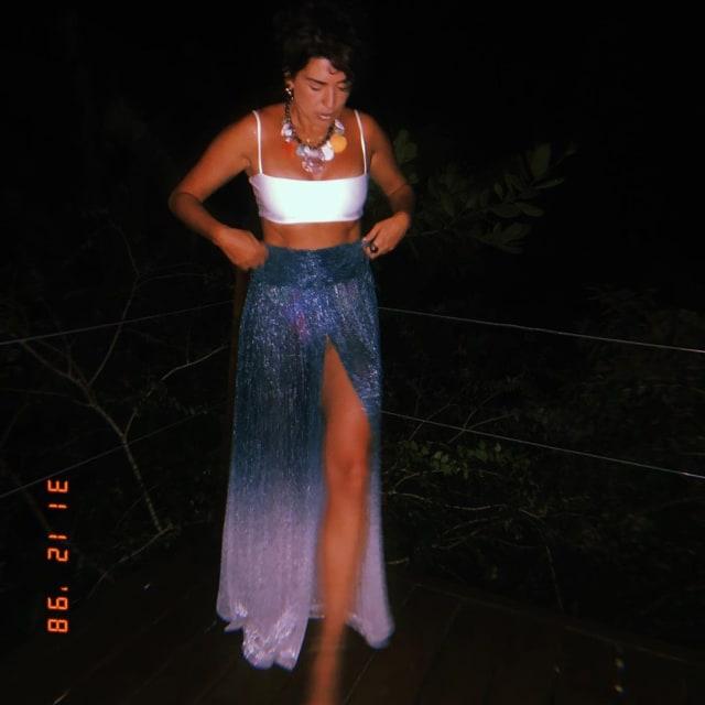 Top branco e saia em azul dégradé foi a escolha de Fernanda Paes Leme, que completou o visual com maxicolar poderoso. A fenda confere sensualidade extra à produção.
